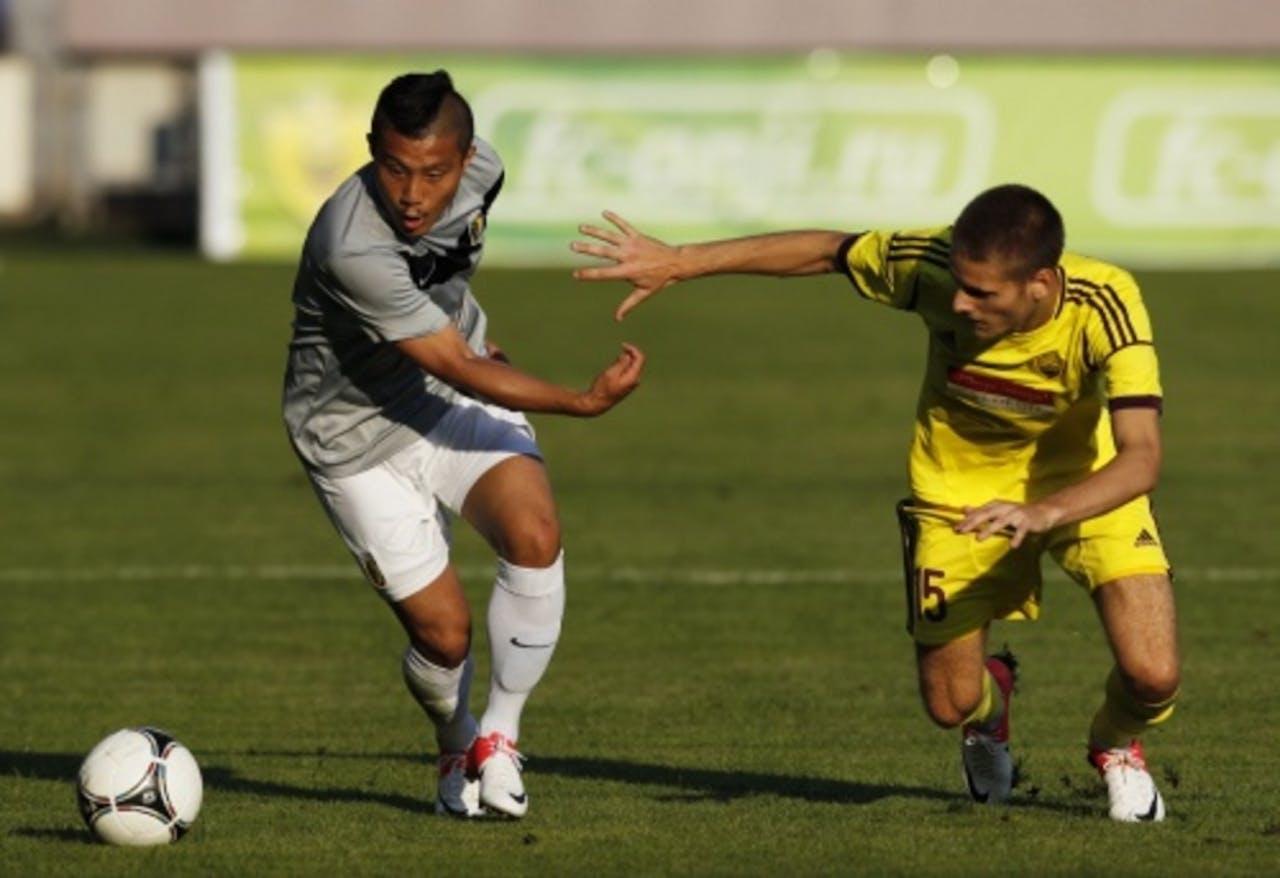 Arseni Logashov (R) vecht om de bal met Michihiro Yasuda van Vitesse. EPA