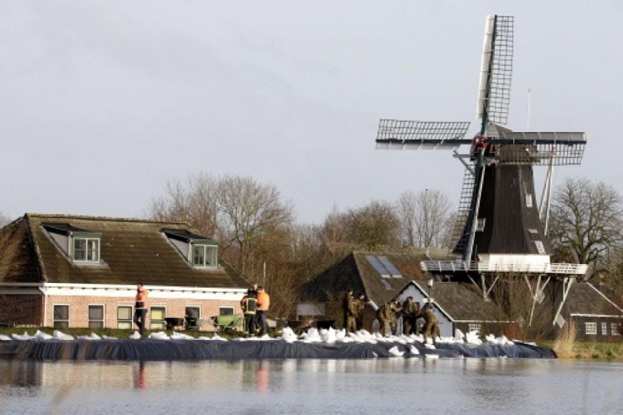 Militairen plaatsten vrijdag zandzakken op de dijk van het Eemskanaal in het dorp Woltersum. ANP