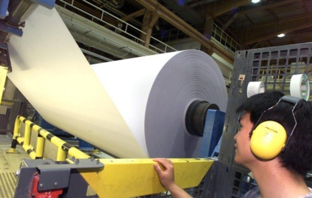 Een mederwerker van Crown van Gelder controleert een papierrol. ANP
