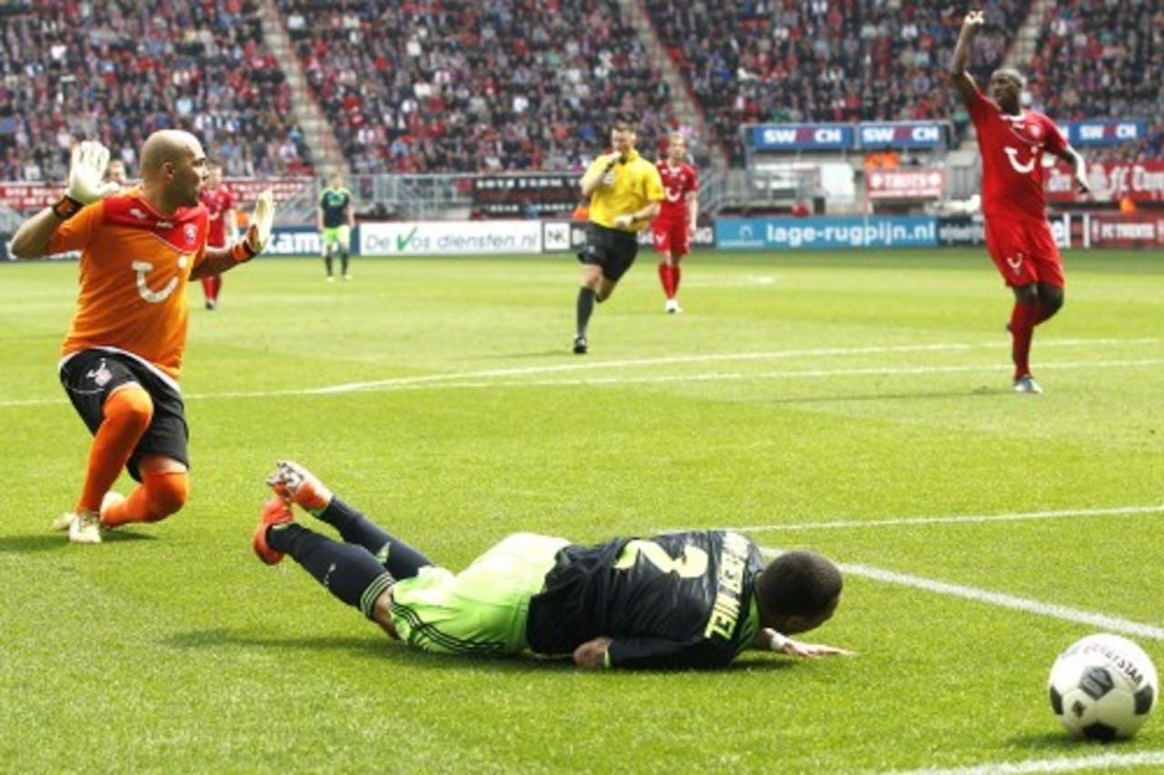 Gregory van der Wiel (M) van Ajax wordt neergelegd door keeper Nicolay Mihaylov (L) van FC Twente.