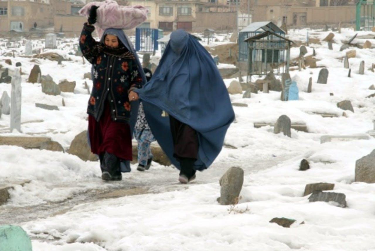 Afghaanse vrouwen op een door sneeuw bedekte begraafplaats in Kabul. EPA