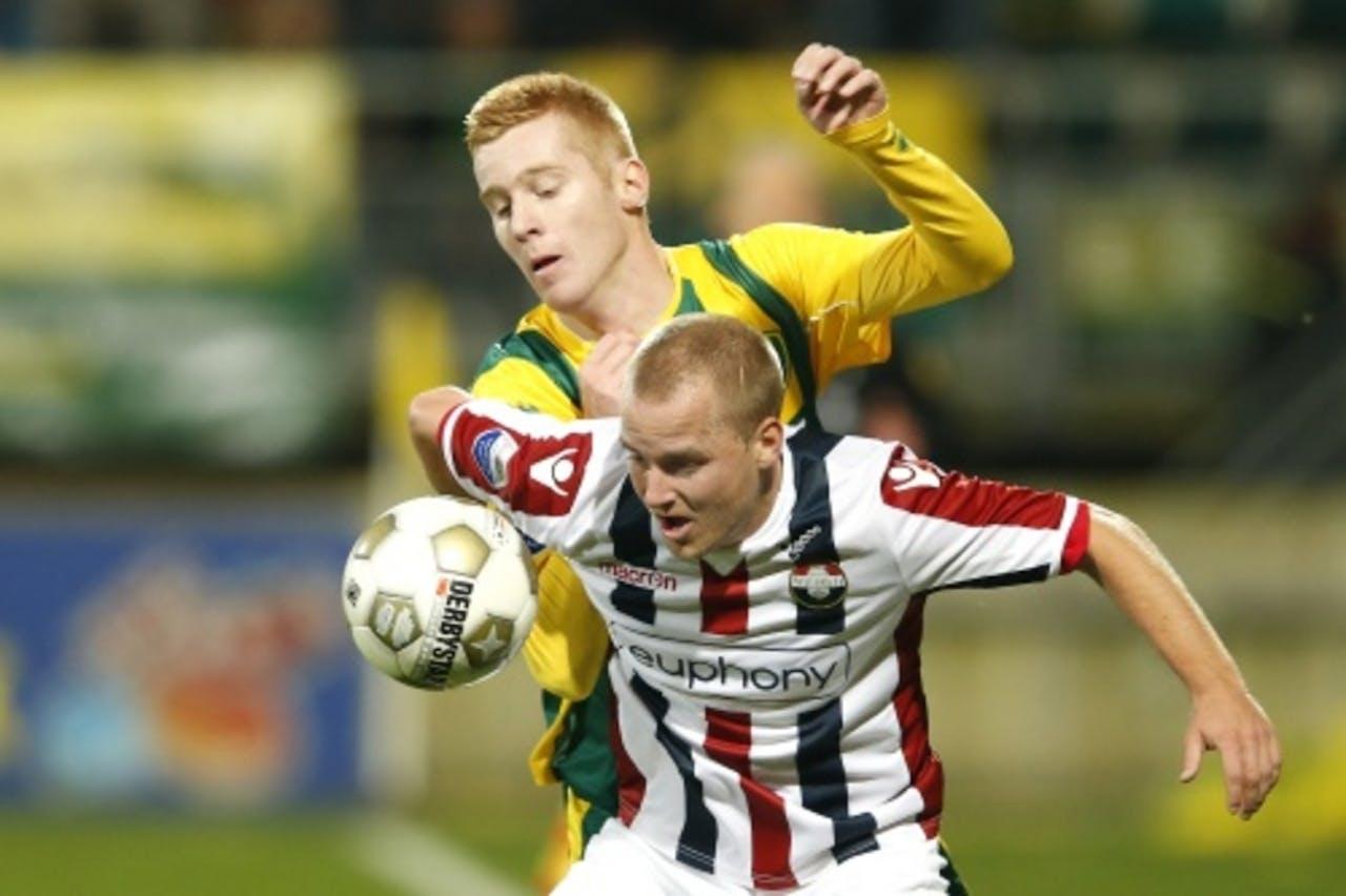 Mike van Duinen (L) van ADO in duel met Kees van Buuren van Willem II. ANP