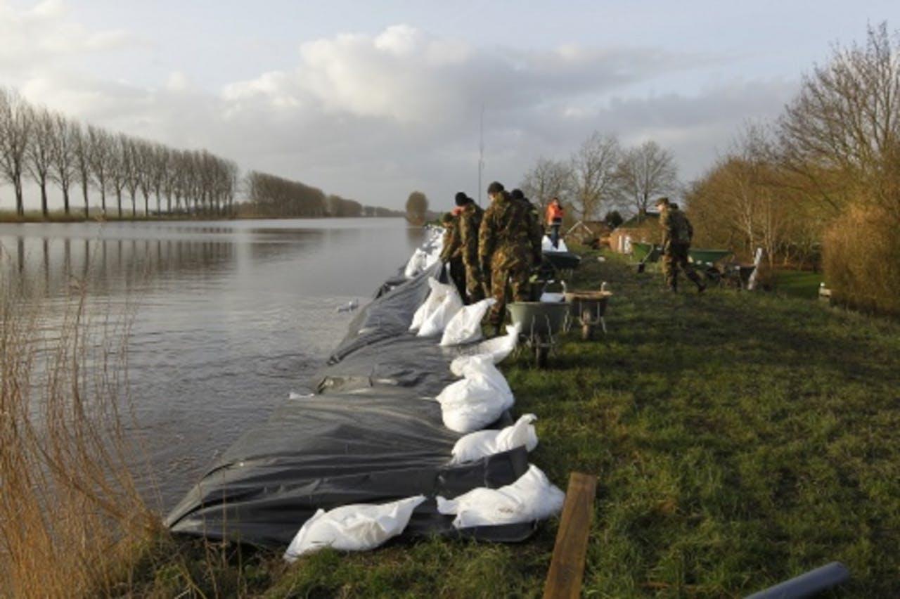 Militairen plaatsen zandzakken op de dijk van het Eemskanaal in het geëvacueerde dorp Woltersum bij de stad Groningen. ANP