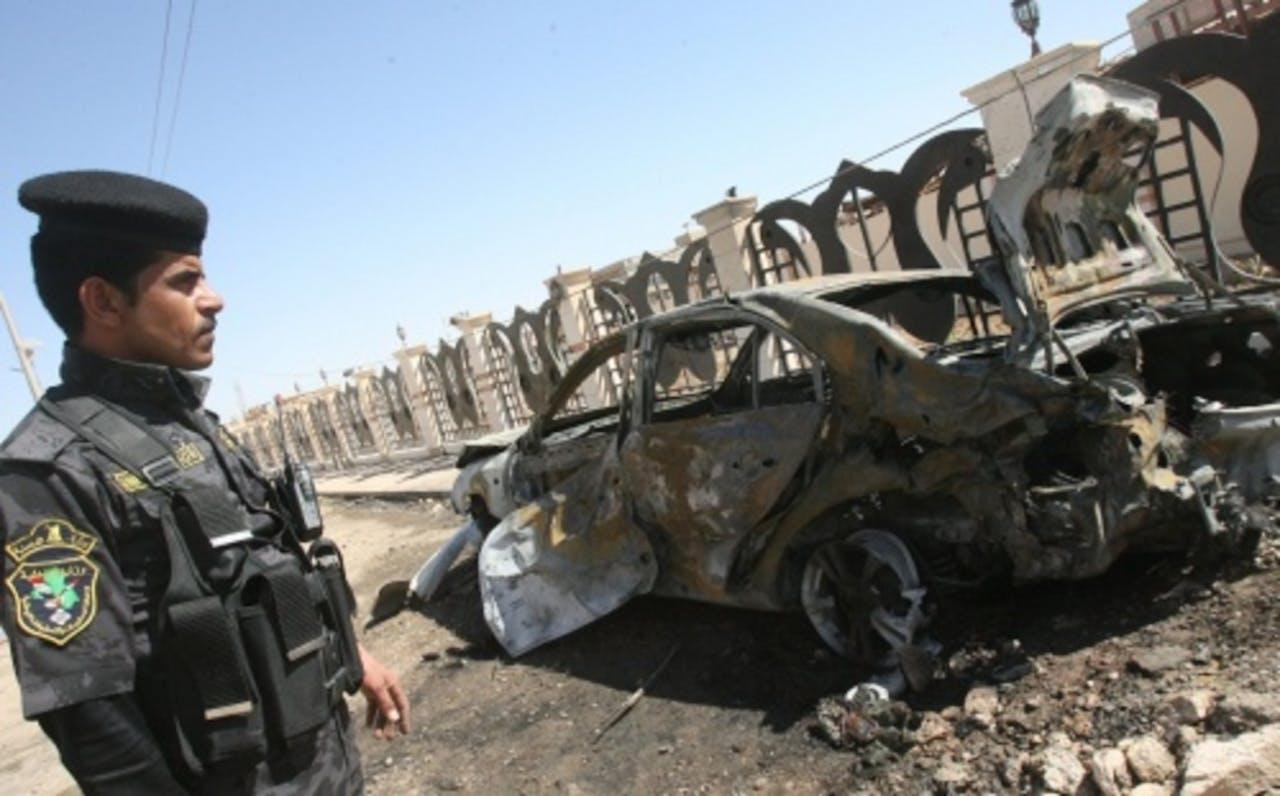 Een Iraakse politieagent kijkt naar een auto die getroffen is door een autobom. EPA
