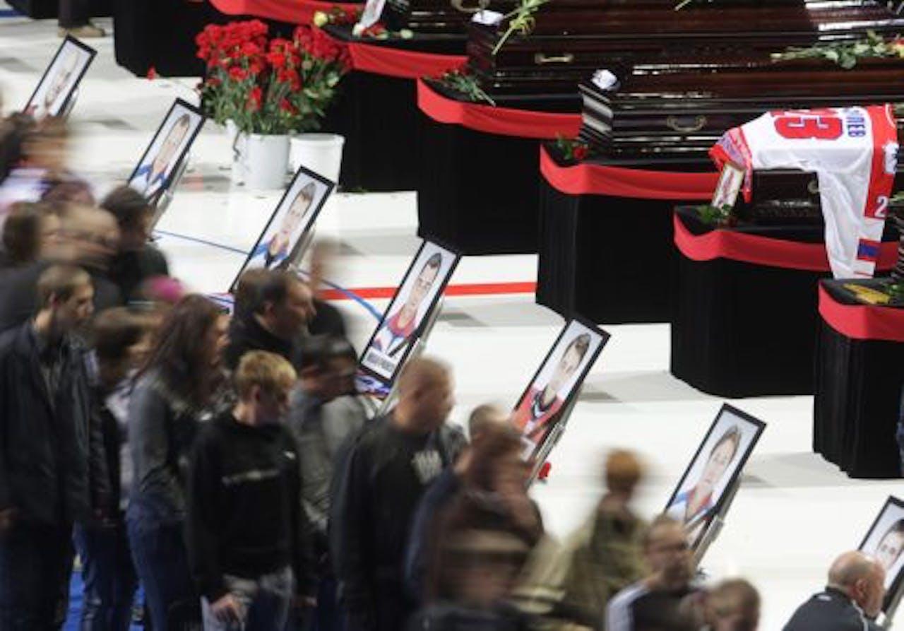 Mensen rouwen bij de kisten van de ijshockeyers die woensdag omkwamen bij het vliegtuigongeluk. EPA
