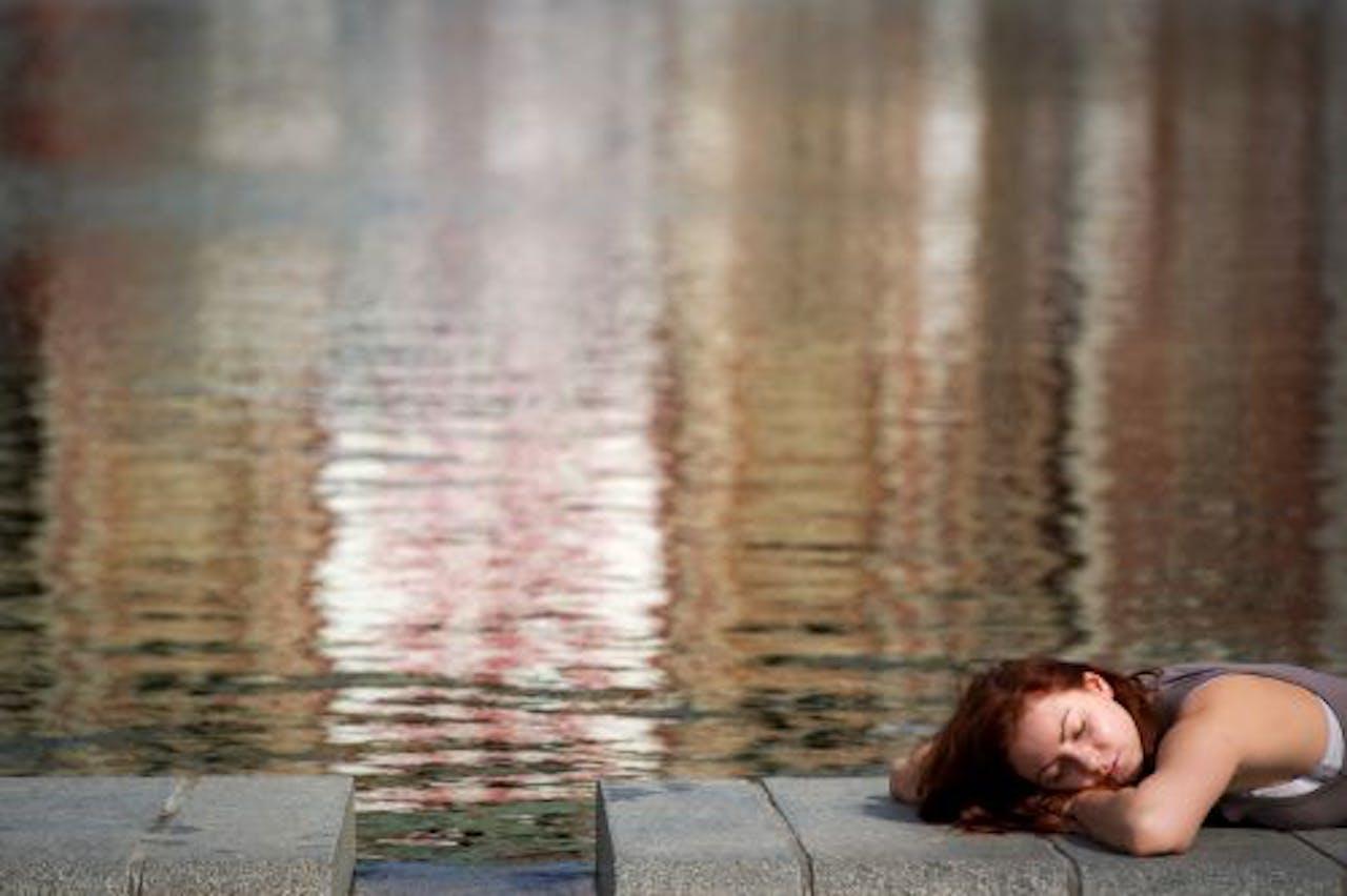 Een vrouw geniet volop van het zomerse weer op het Museumplein in Amsterdam. ANP