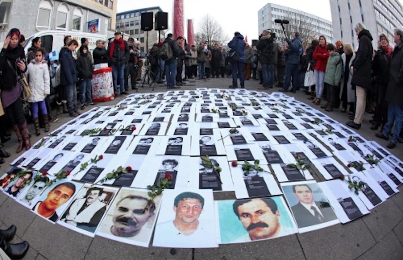 Foto's van slachtoffers van de 'dönermoorden' liggen zaterdag op straat voordat er een stille tocht wordt gehouden in Hamburg. EPA