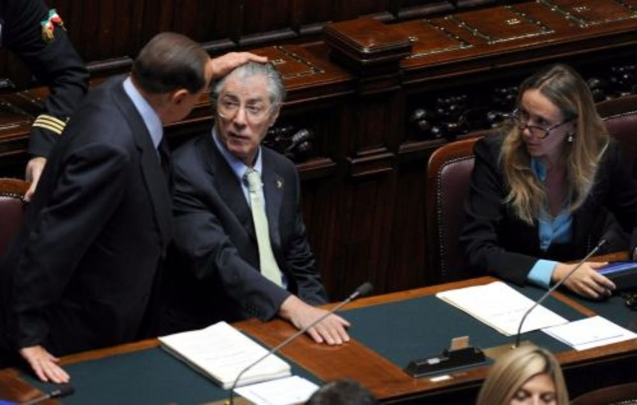 Silvio Berlusconi (L) geeft Umberto Bossi een aai over de bol. EPA