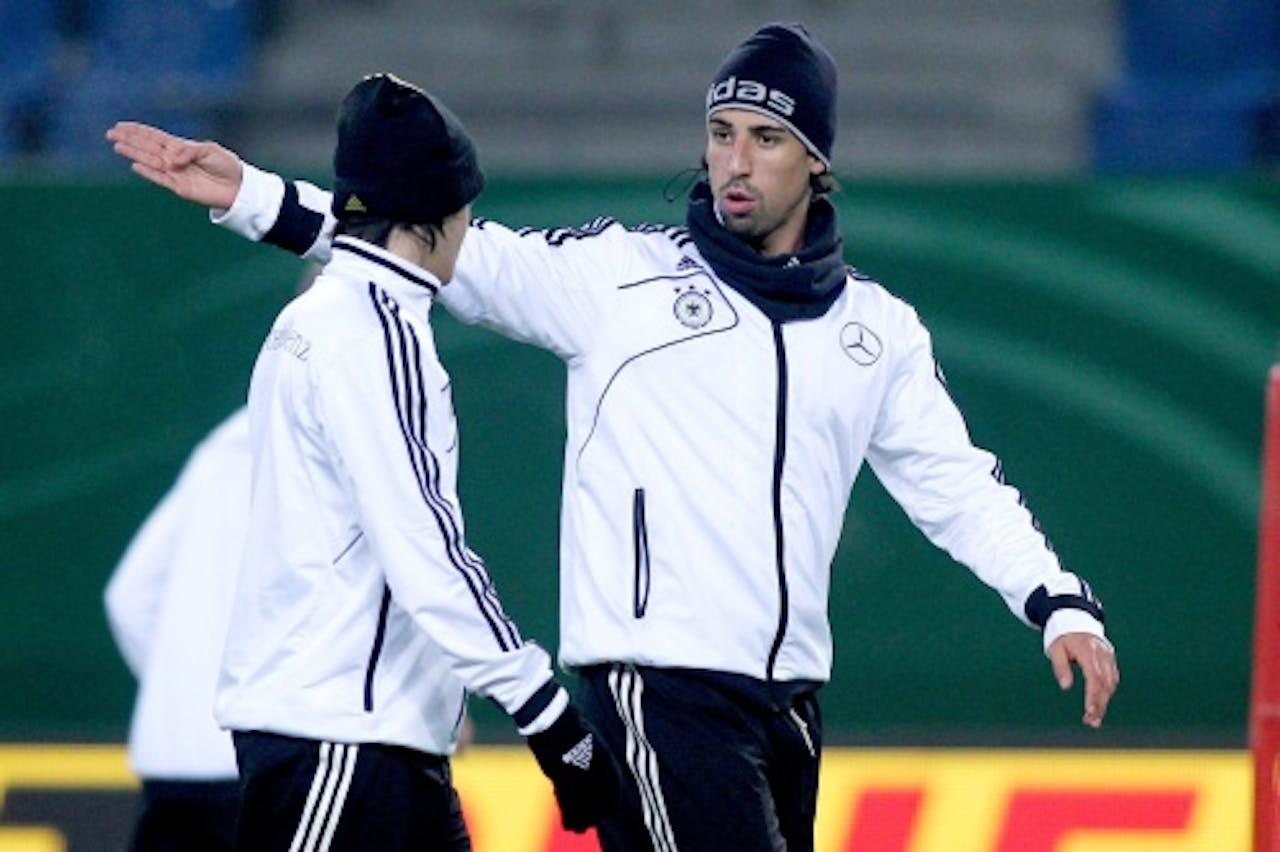 Mesut Oezil (L) en Sami Khedira maandag tijdens de training van het Duitse elftal in Hamburg. EPA