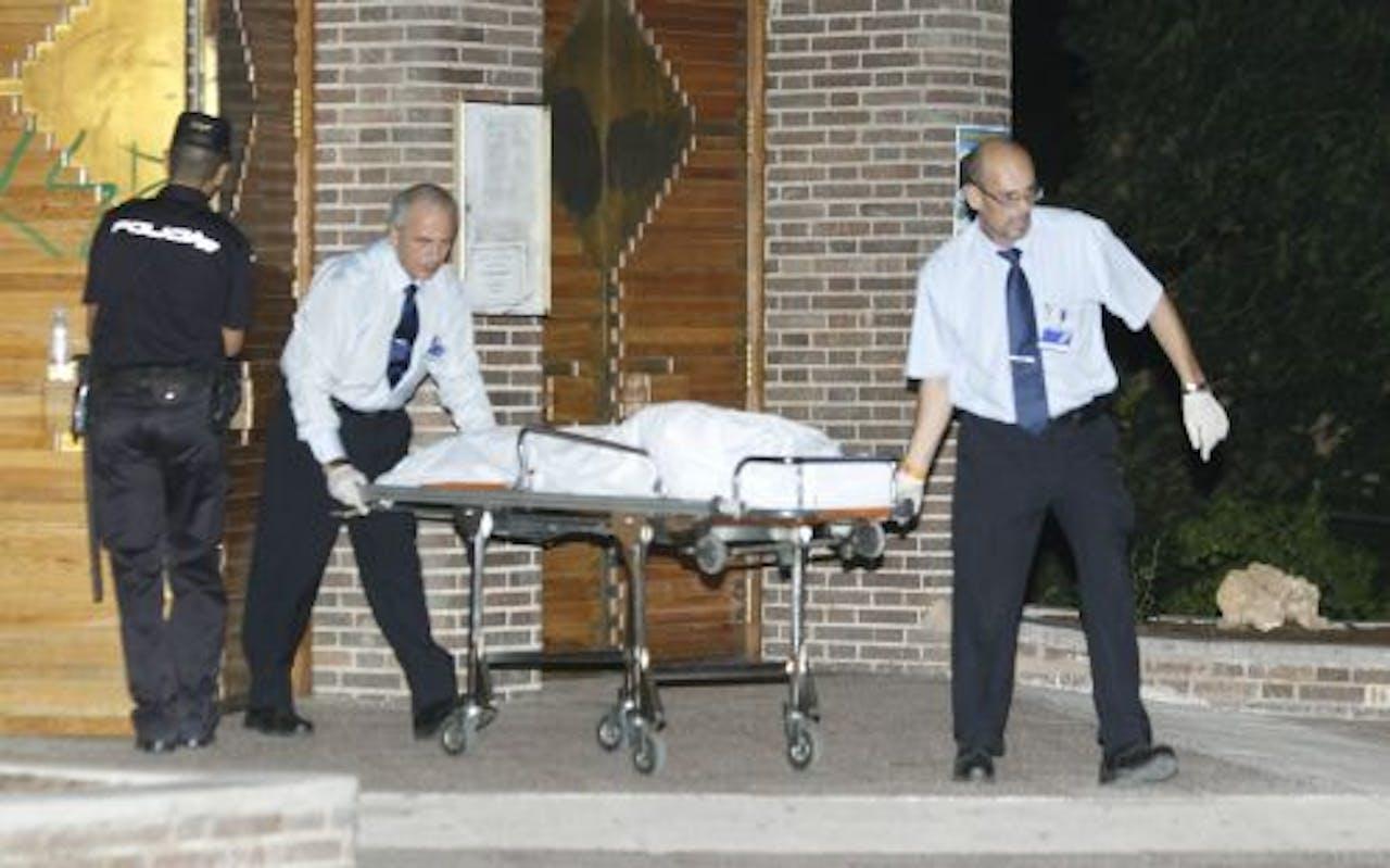 Het lichaam van de vrouw wordt uit de kerk gehaald. EPA