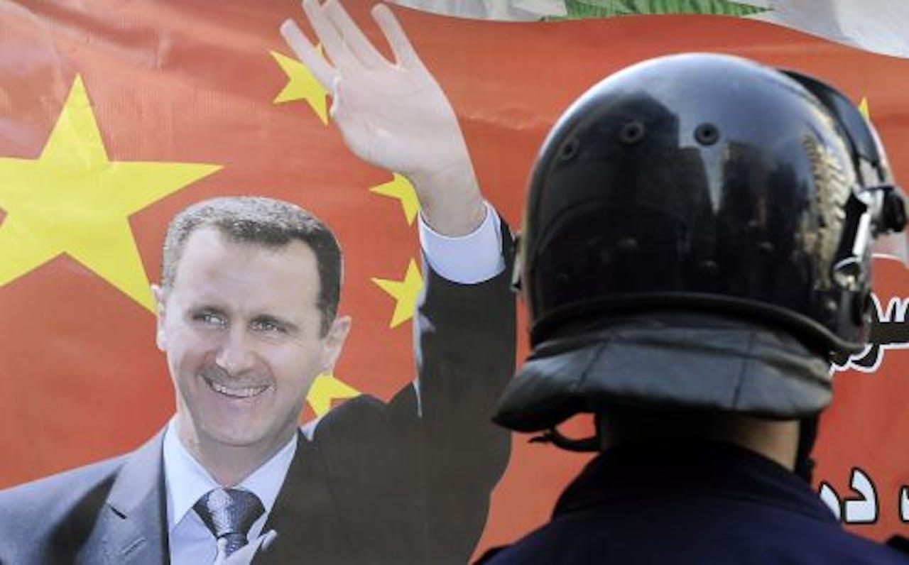 Een Syrische politieman staat bij een poster van president Assad (archieffoto 23 oktober). EPA
