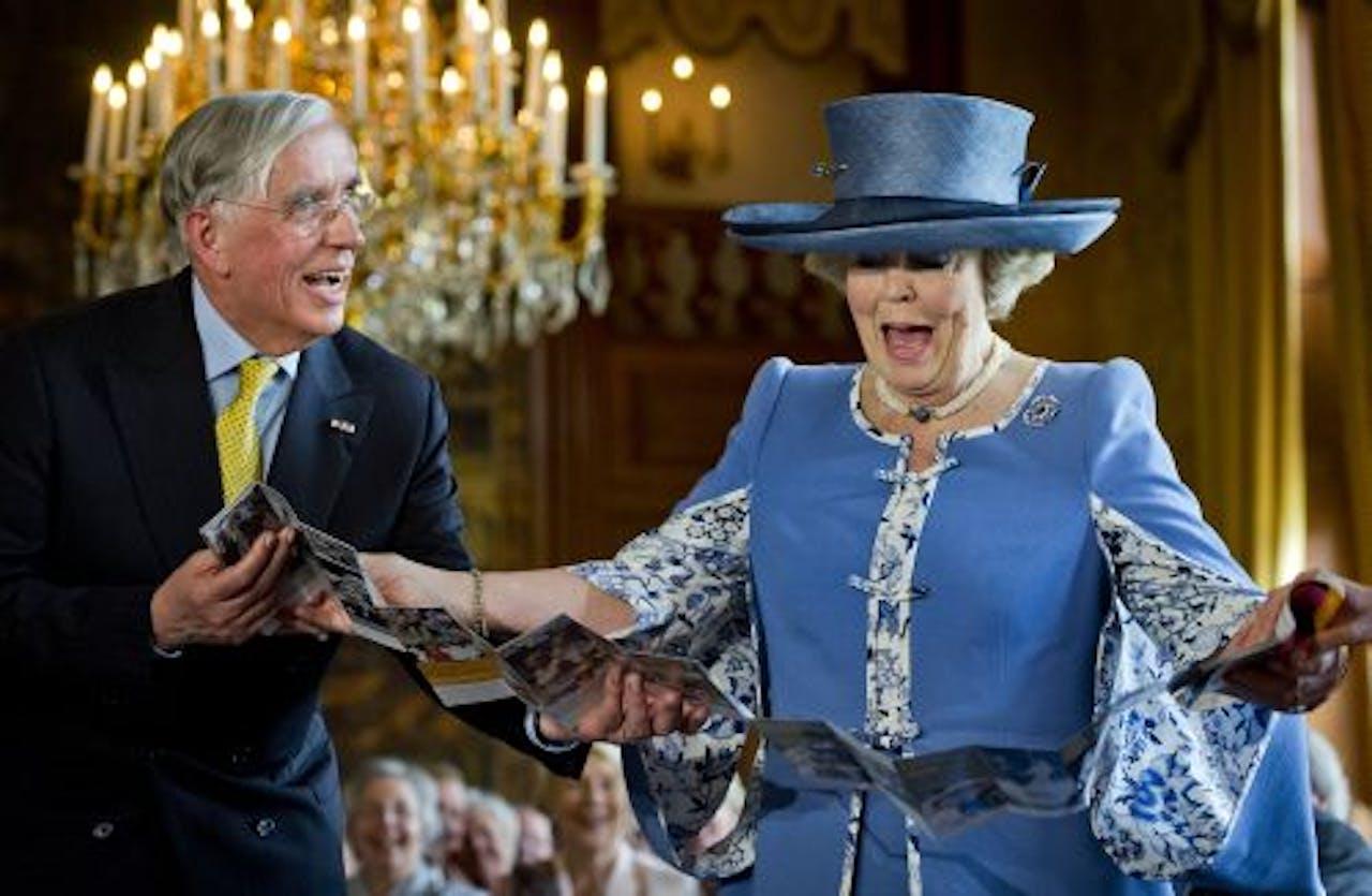 Koningin Beatrix verricht zaterdag op Paleis Het Loo de openingshandeling van de tentoonstelling 'Máxima, 10 jaar in Nederland' door met de directeur van Nationaal Museum Paleis Het Loo, J. ter Molen, een boekje te ontvouwen. ANP