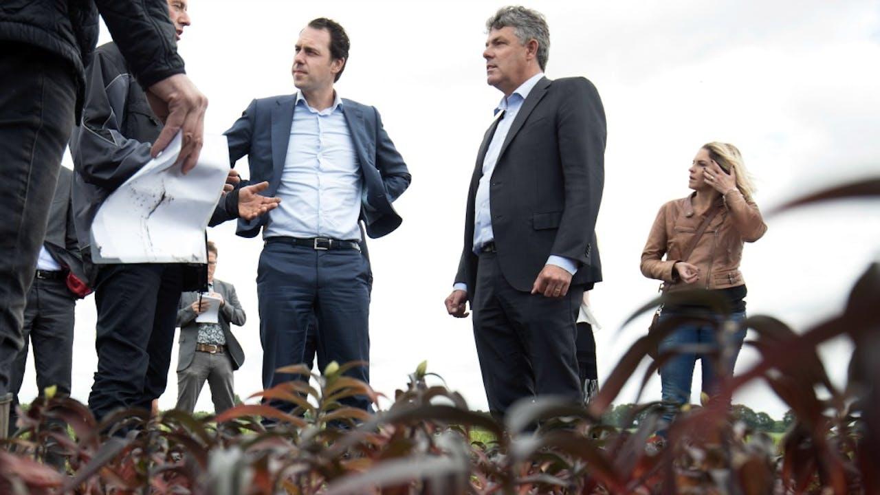Staatssecretaris Van Dam (3de van rechts) inspecteert de schade bij gedupeerden. Foto: ANP