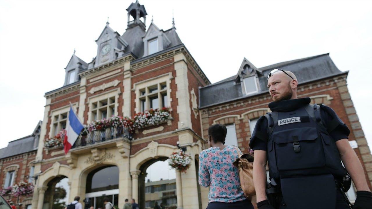 Een politieagent houdt wacht bij de kerk in Saint-Etiènne-du-Rouvray. Foto ANP