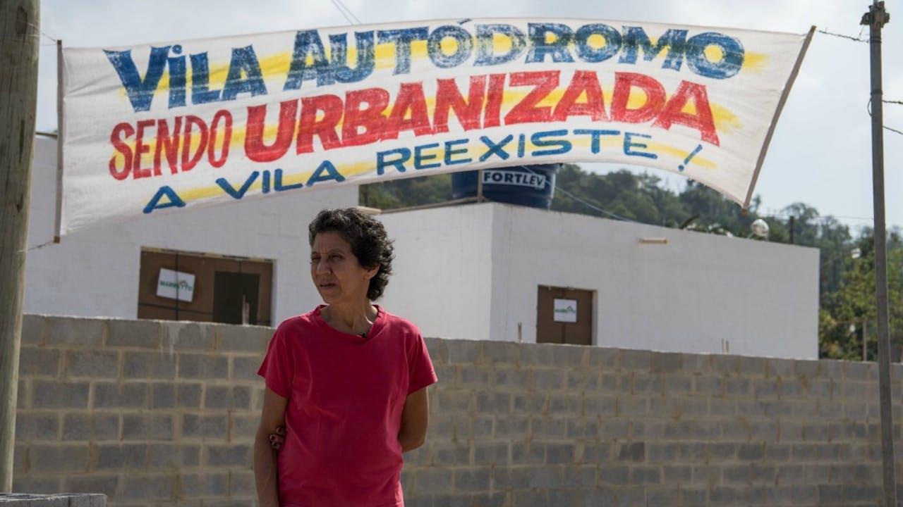 Een bewoonster van de favela Vila Autódromo poseert voor de nieuwbouw. Foto ANP