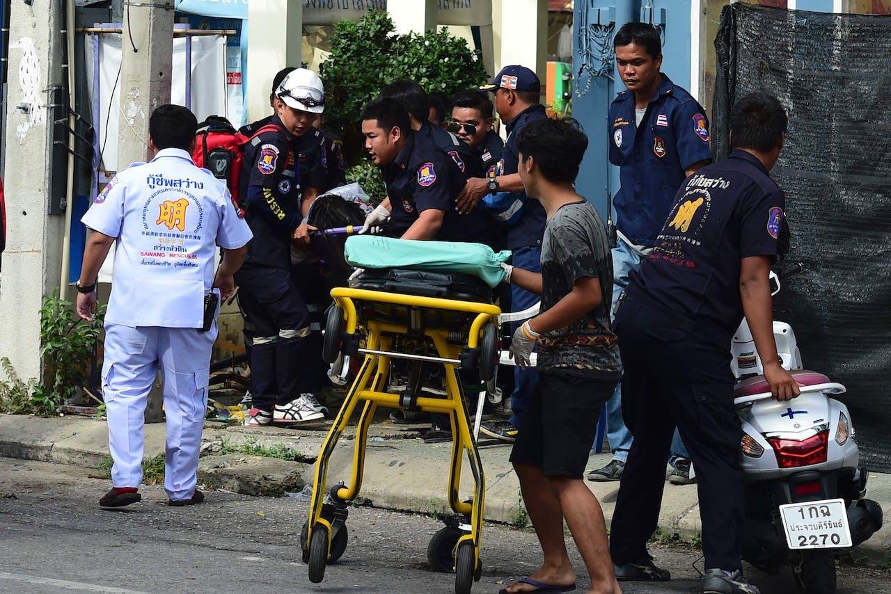 Thaise hulpdiensten helpen een gewonden na een van de aanslagen in Hua Hin in Thailand. Foto AFP