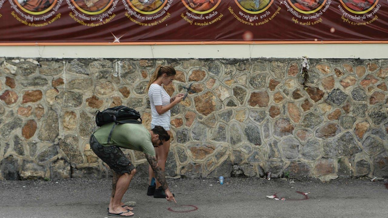 Toeristen nemen een kijkje bij de plaats van een bomaanslag in Hua Hin.