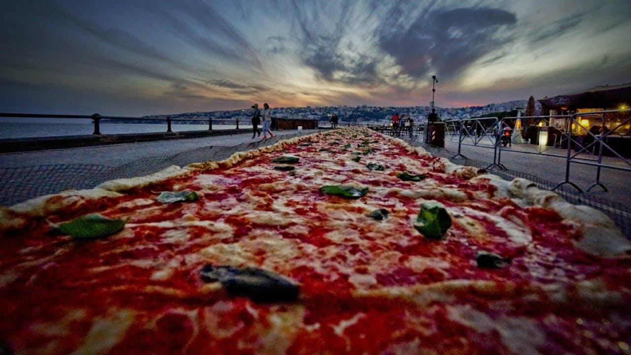 Deze pizza langs de kust van Napels probeerde met 2 kilometer lengte het wereldrecord langste pizza ooit te verbreken. Foto ANP