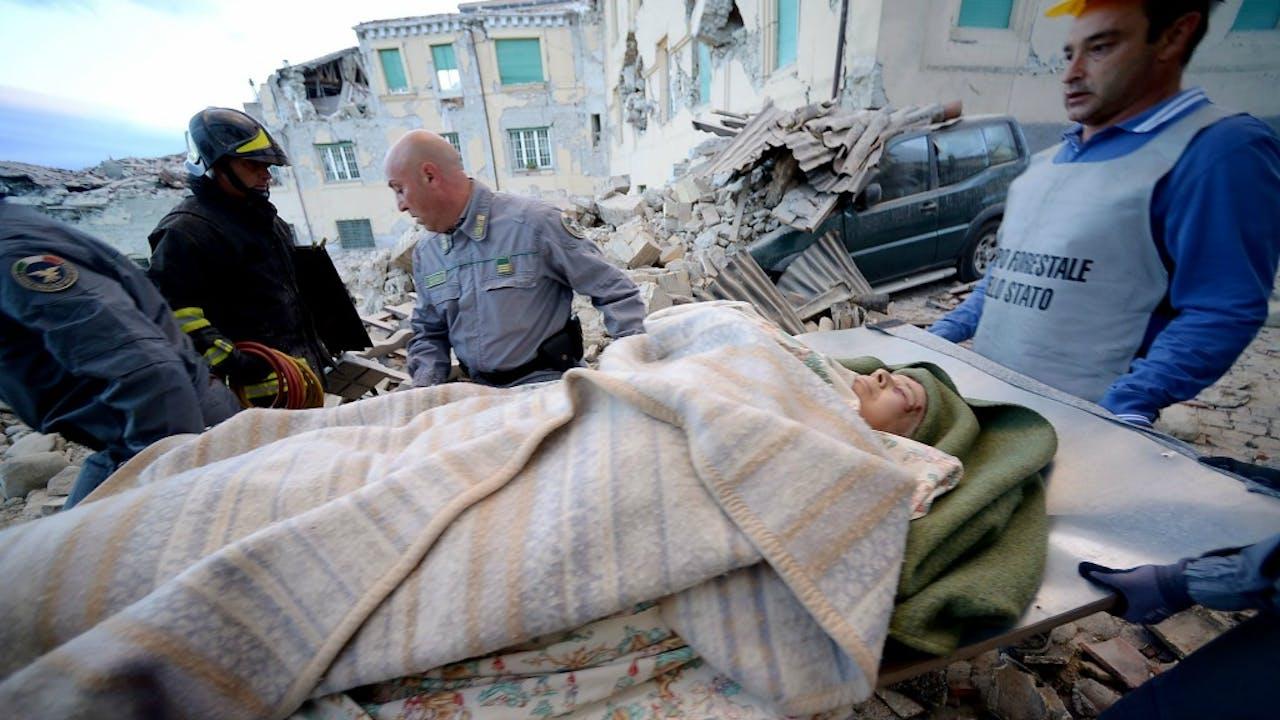 In Amatrice dragen de reddingswerkers een man weg na de aardbeving. Bron: ANP