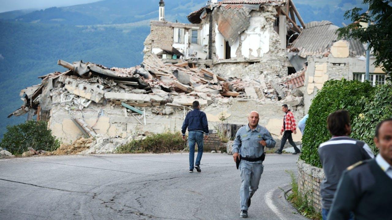 Hulpdiensten en slachtoffers lopen langs de resten in Amatrice. Bron: ANP