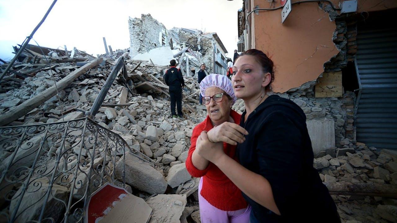 Inwoners reageren geschokt op de ravage na de aardbeving in Amatrice. Bron: ANP