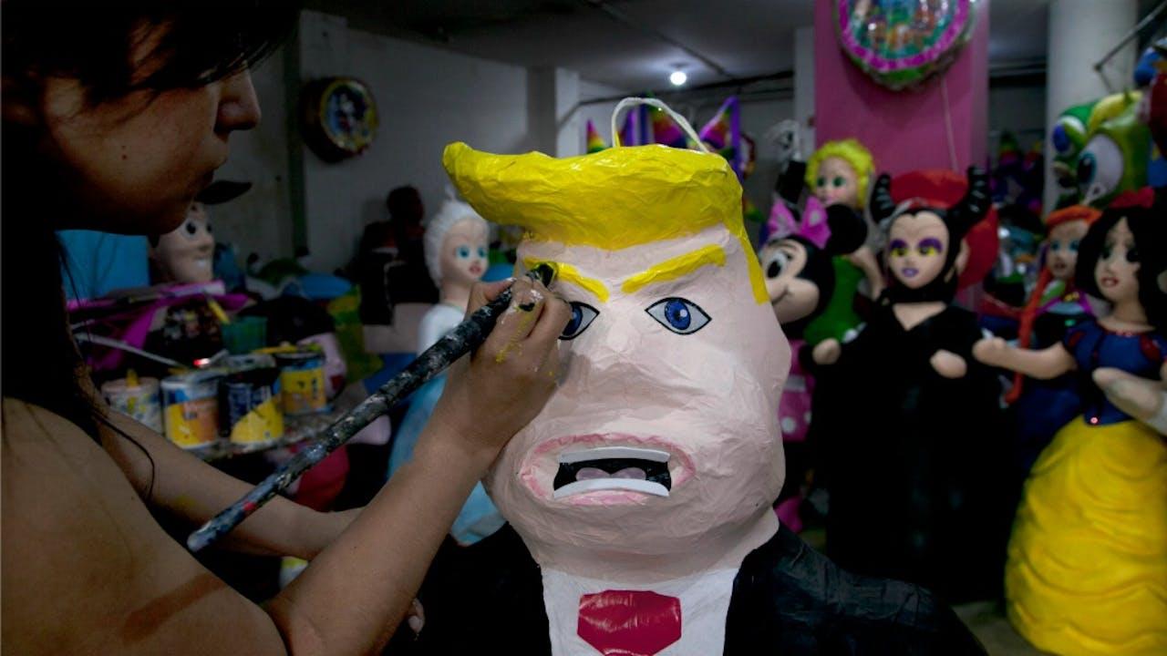 Een mexicaanse vrouw schildert een Trump-piñata