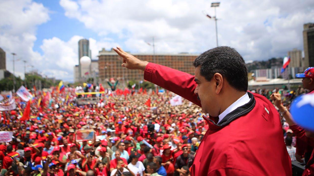 Terwijl er verderop wordt geprotesteerd tegen hem, zwaait president Nicolas Maduro zwaait zijn aanhangers toe. ANP/AFP/MARCELO GARCIA