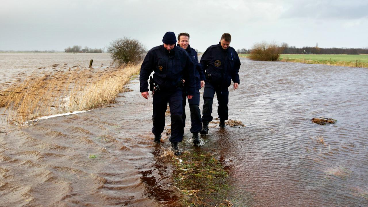 Politieagenten lopen door het water dat over een dijk is gelopen. Een dijkdoorbraak dreigde bij Tolbert (Foto: ANP, 2012)