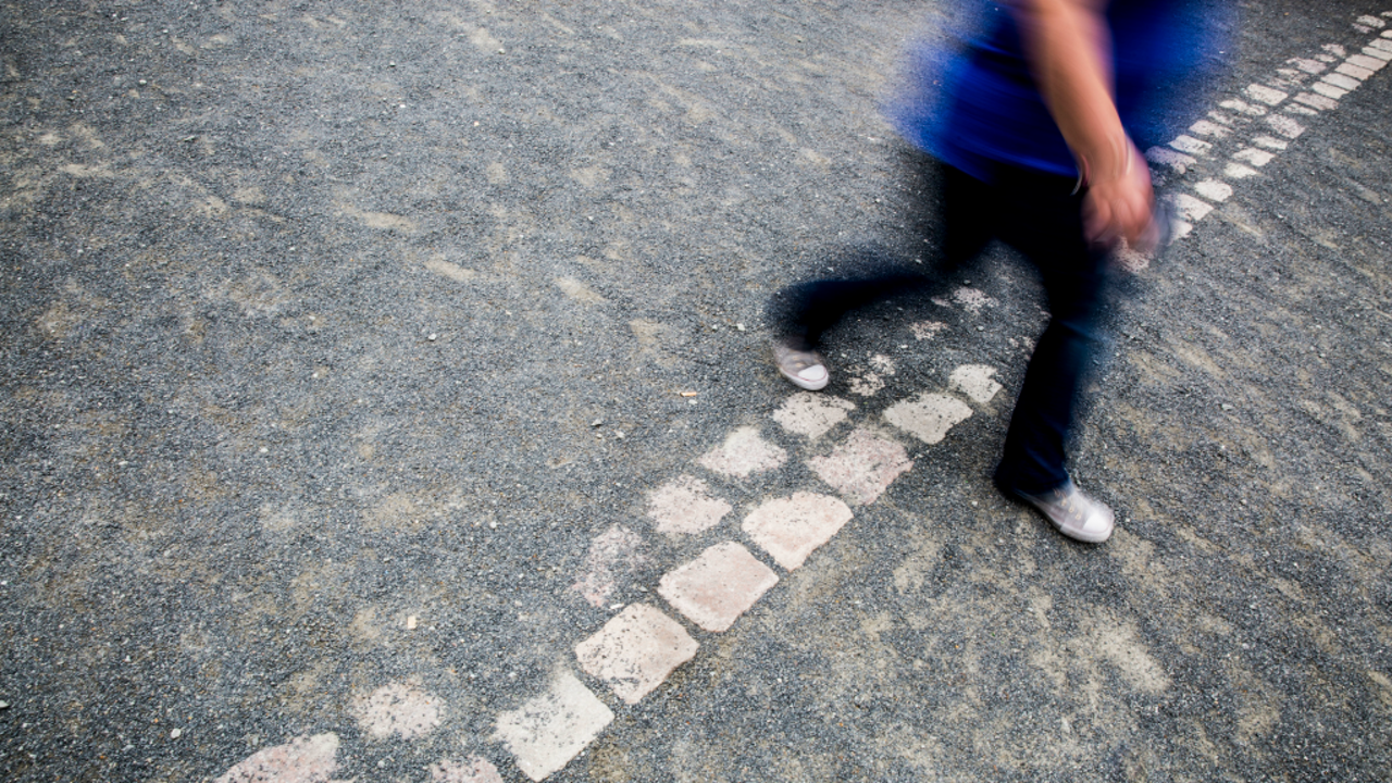 Een vrouw stapt over de plek waar ooit de Berlijnse muur stond (Foto: Rob Voss/HH)