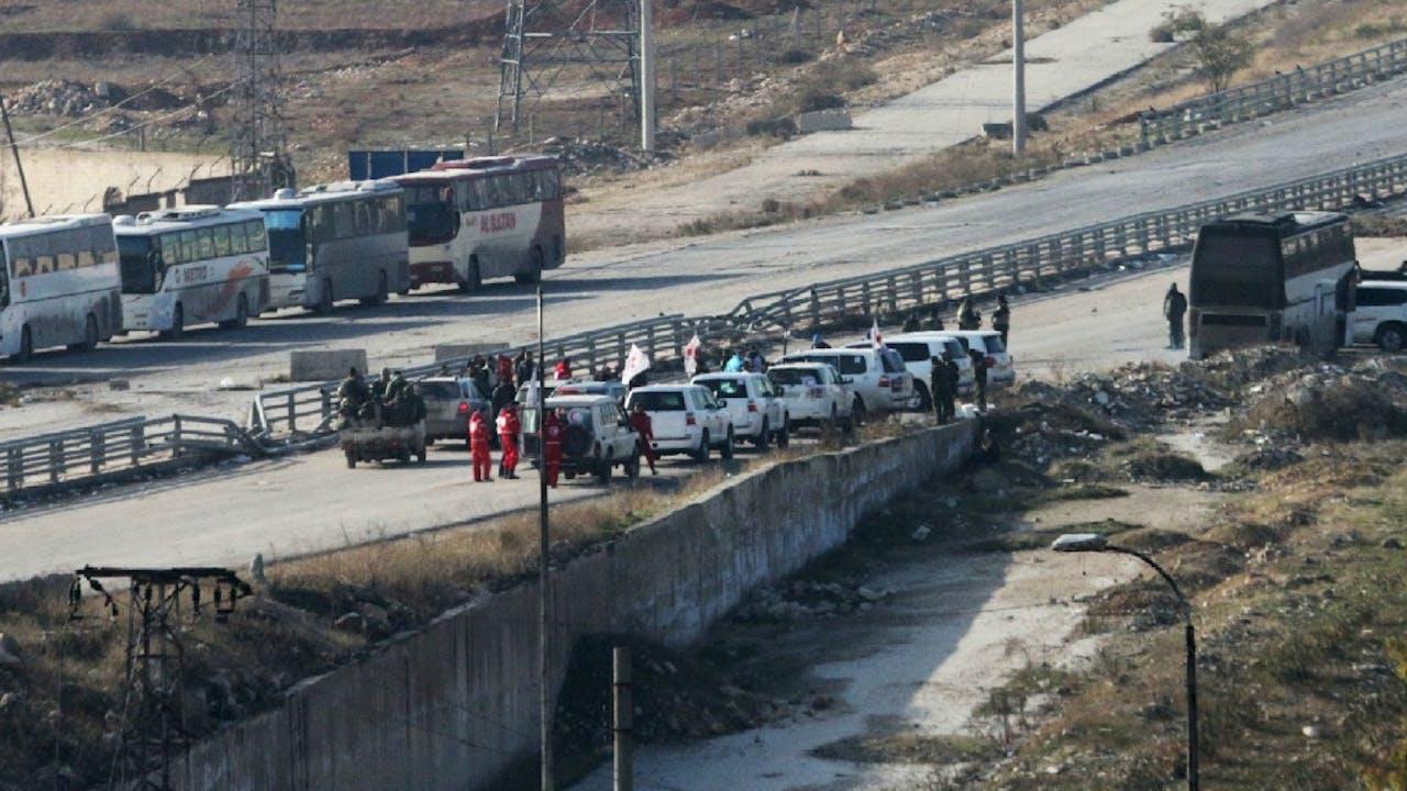 Voertuigen van hulporganisaties vandaag bij een wachtpost van de regering ten zuiden van Aleppo. ANP/AFP