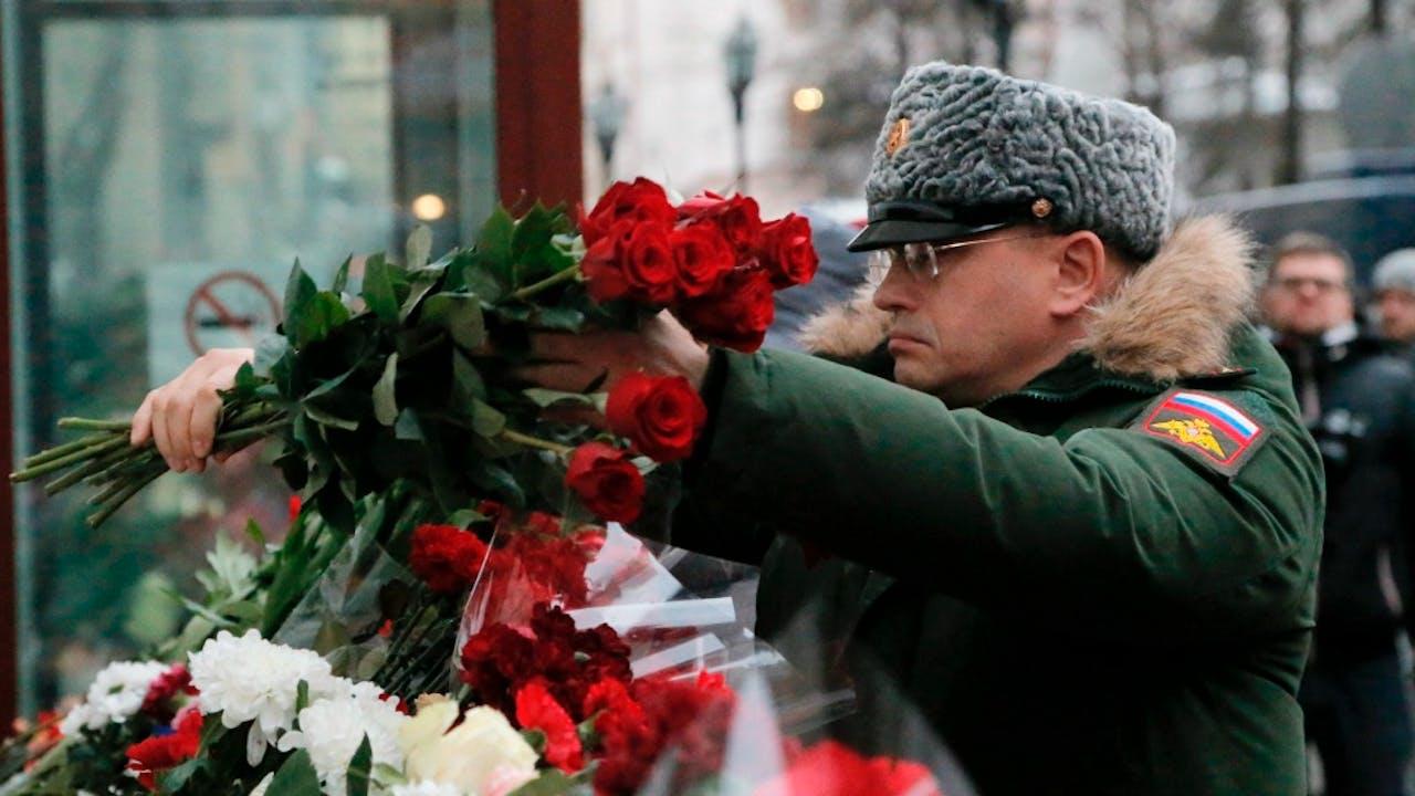 Een Russische soldaat legt bloemen bij een herdenkingsplek voor de omgekomen koorleden van het Alexandrov Ensemble. Foto ANP