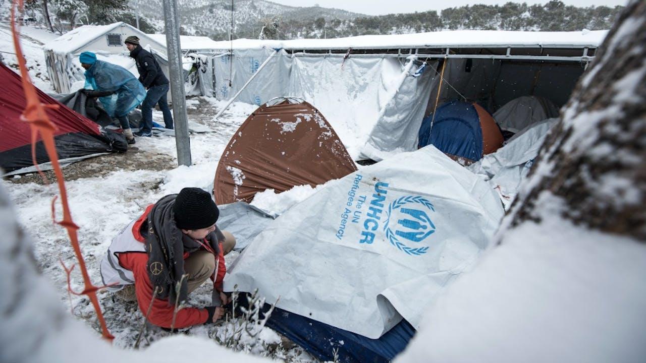 Vrijwilligers helpen een ingestorte tent in vluchtelingenkamp Moria weer overeind. Foto: HH/Bas Bakkenes
