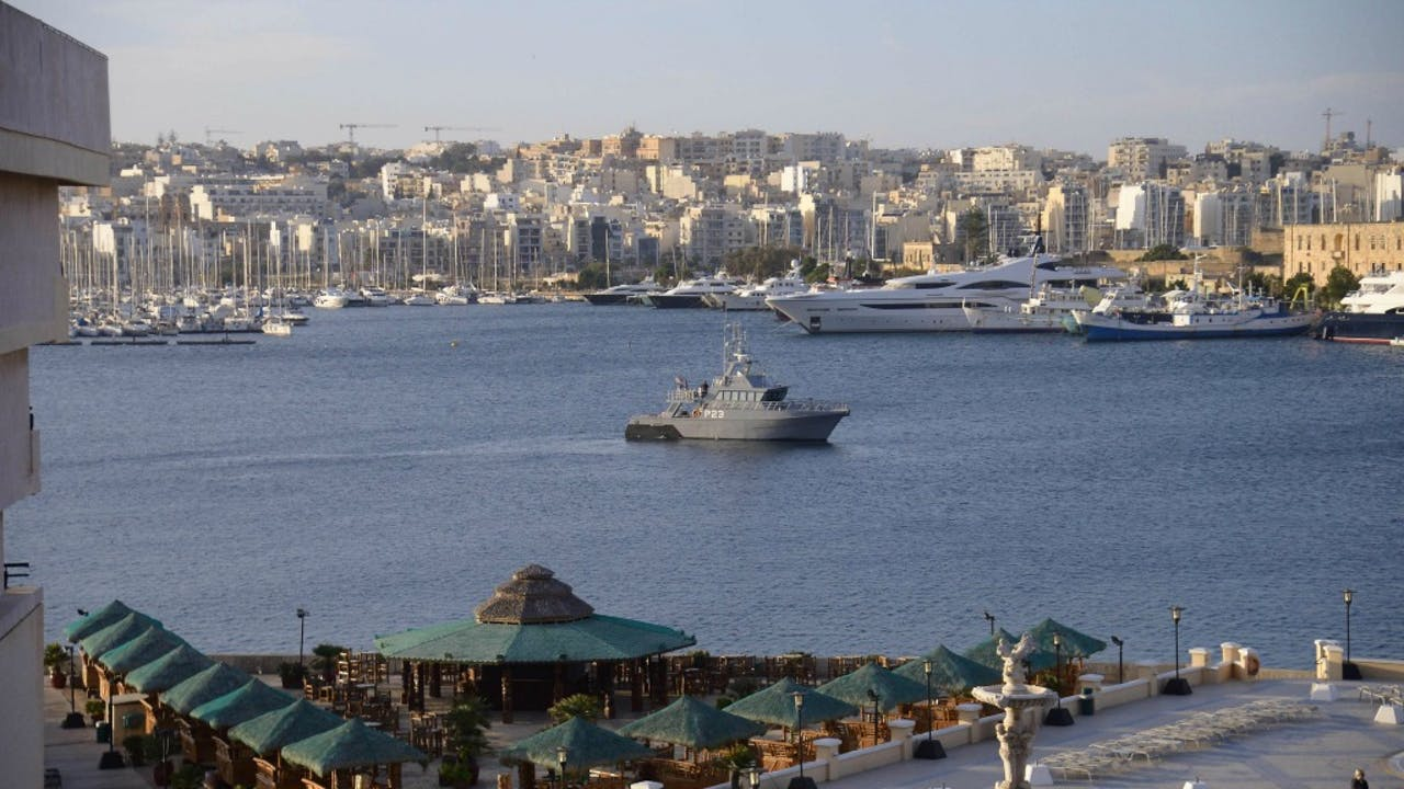 Een schip patrouilleert in de haven van Malta aan de vooravond van de Europese top. Foto ANP