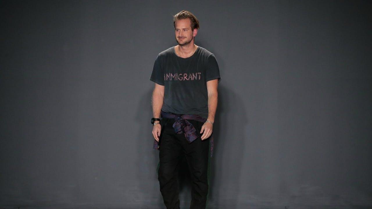 31 Januari: ontwerper Robert Geller in zijn 'immigrant'- T-shirt. Foto: ANP/AFP