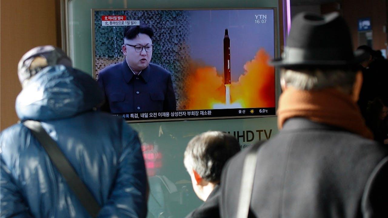 Zuid-Koreanen zien op tv het nieuws over de raketlancering. Foto: ANP/EPA