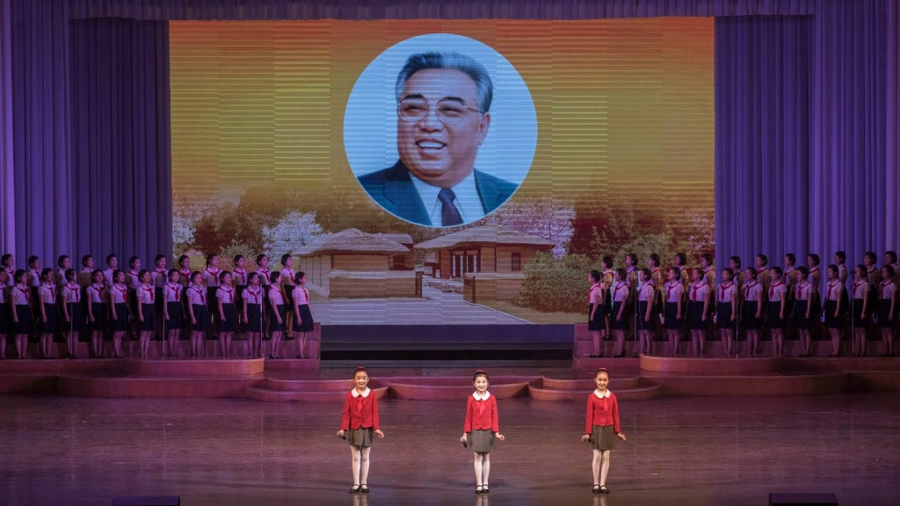 Kinderen doen een opvoering in Pyongyang, met op de achtergrond een portret van Kim Il-sung. Foto: ANP/AFP