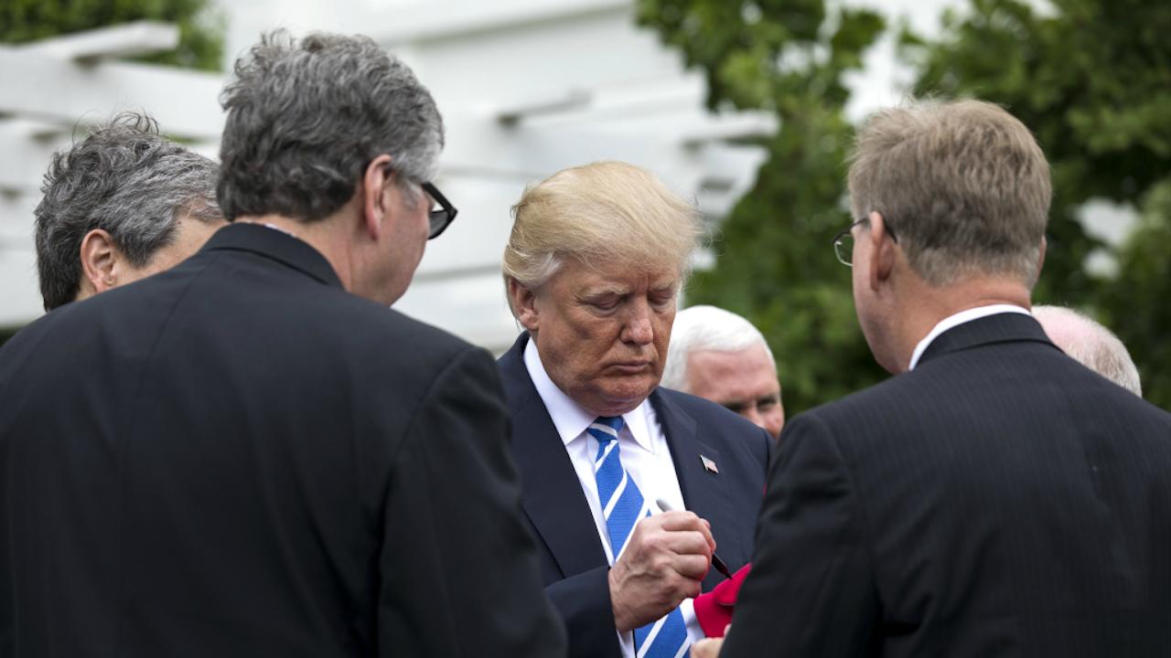 President Trump signeert een hoed (Foto: ANP)