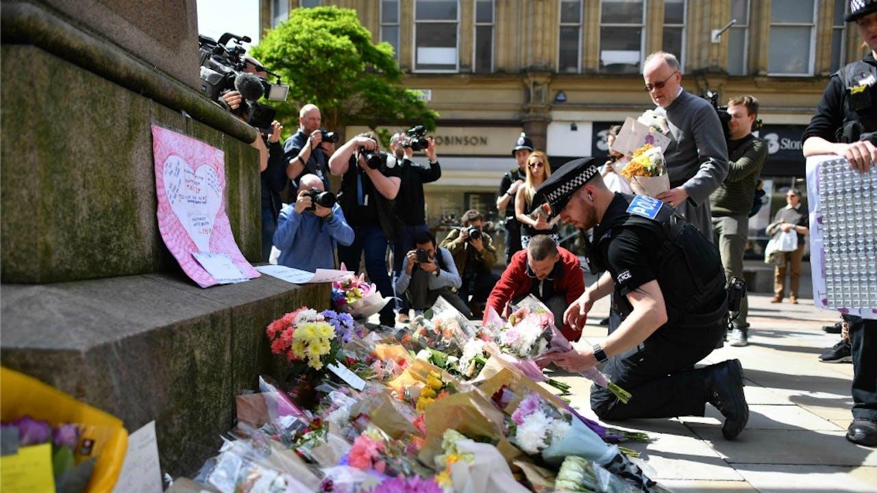 Politieagenten herschikken bloemen die op St Ann's Square in Manchester zijn neergelegd ter nagedachtenis van de slachtoffers van de aanslag gisteravond bij Manchester Arena. Foto ANP