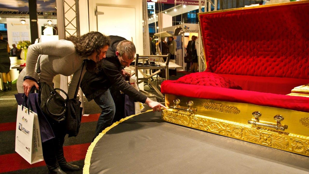 Bezoekers kijken naar een 24 karaats gouden kist op de Uitvaart Vakbeurs. Foto ANP