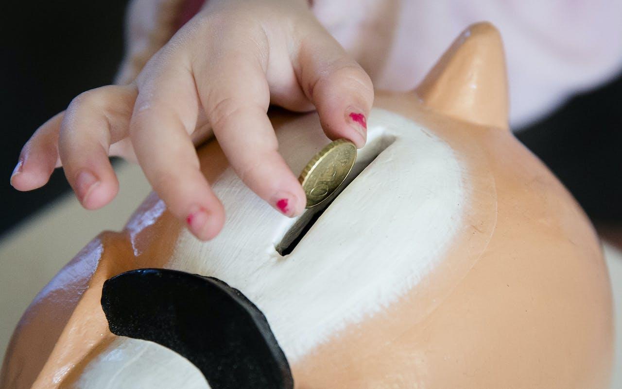 Een meisje stopt geld in haar spaarpot.