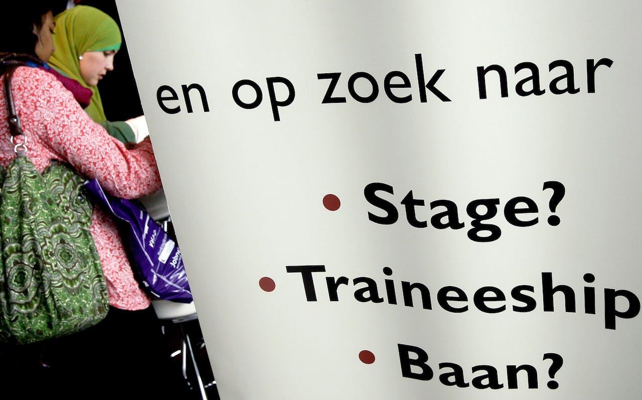 Twee vrouwen bekijken een informatiefolder dinsdag op het evenement DiversityWorks in Amsterdam.