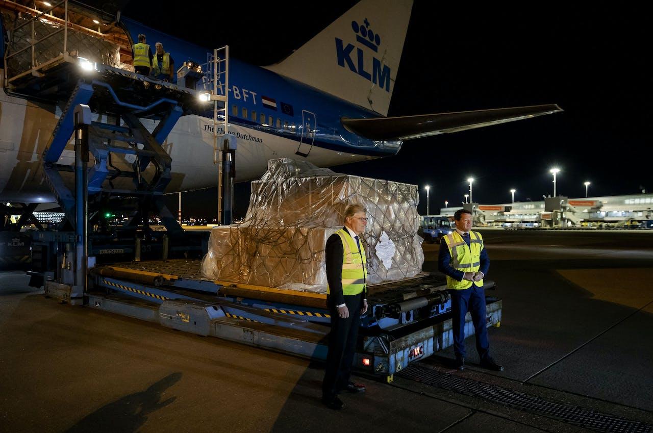 Topman Pieter Elbers (r) van KLM en minister Martin van Rijn voor Medische Zorg poseren naast een nieuwe lading Chinese mondkapjes.