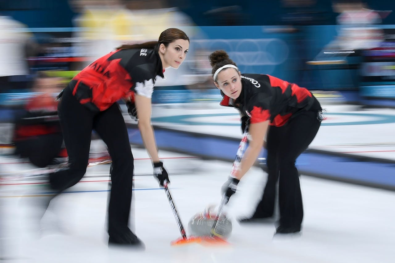 2018-02-20 14:25:15 Canada's Lisa Weagle (L) and Joanne Courtney brush in front of the stone during the curling women's round robin session between Canada and China during the Pyeongchang 2018 Winter Olympic Games at the Gangneung Curling Centre in Gangneung on February 20, 2018. / AFP PHOTO / WANG Zhao
