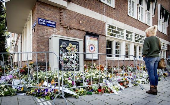 Een passant kijkt bij de bloemen die zijn neergelegd bij het kantoor van de doodgeschoten advocaat Derk Wiersum.