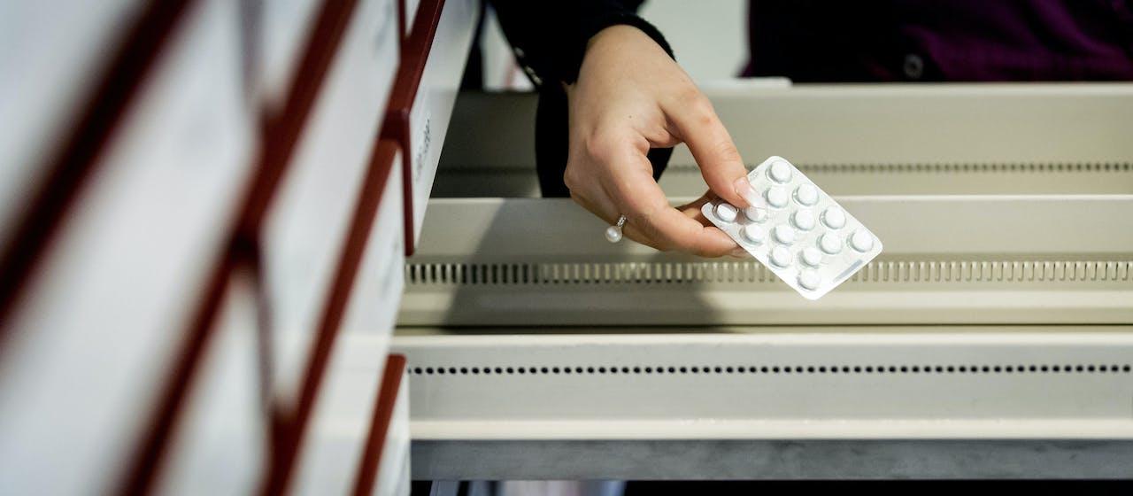 Een apothekersassistente zoekt medicijnen bij elkaar in een apotheek.