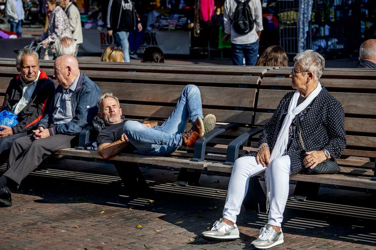 Mensen genieten van het mooie weer op zaterdag begin oktober in het centrum van Rotterdam