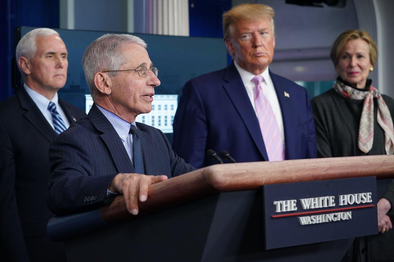 Donald Trump kijkt toe hoe zijn 'coronadokter' Fauci de pers toespreekt.