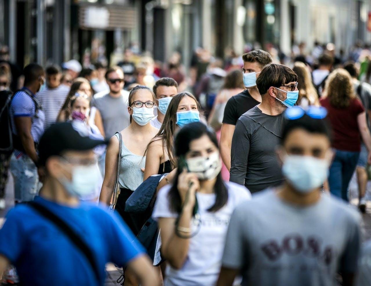 Winkelend publiek in de Kalverstraat. Het dragen van een mondkapje is verplicht op vijf drukke plekken in de stad, waaronder de Dam en de Kalverstraat.