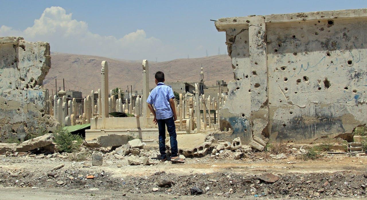 Een jongen kijkt naar een begraafplaats in Douma, Syrië.