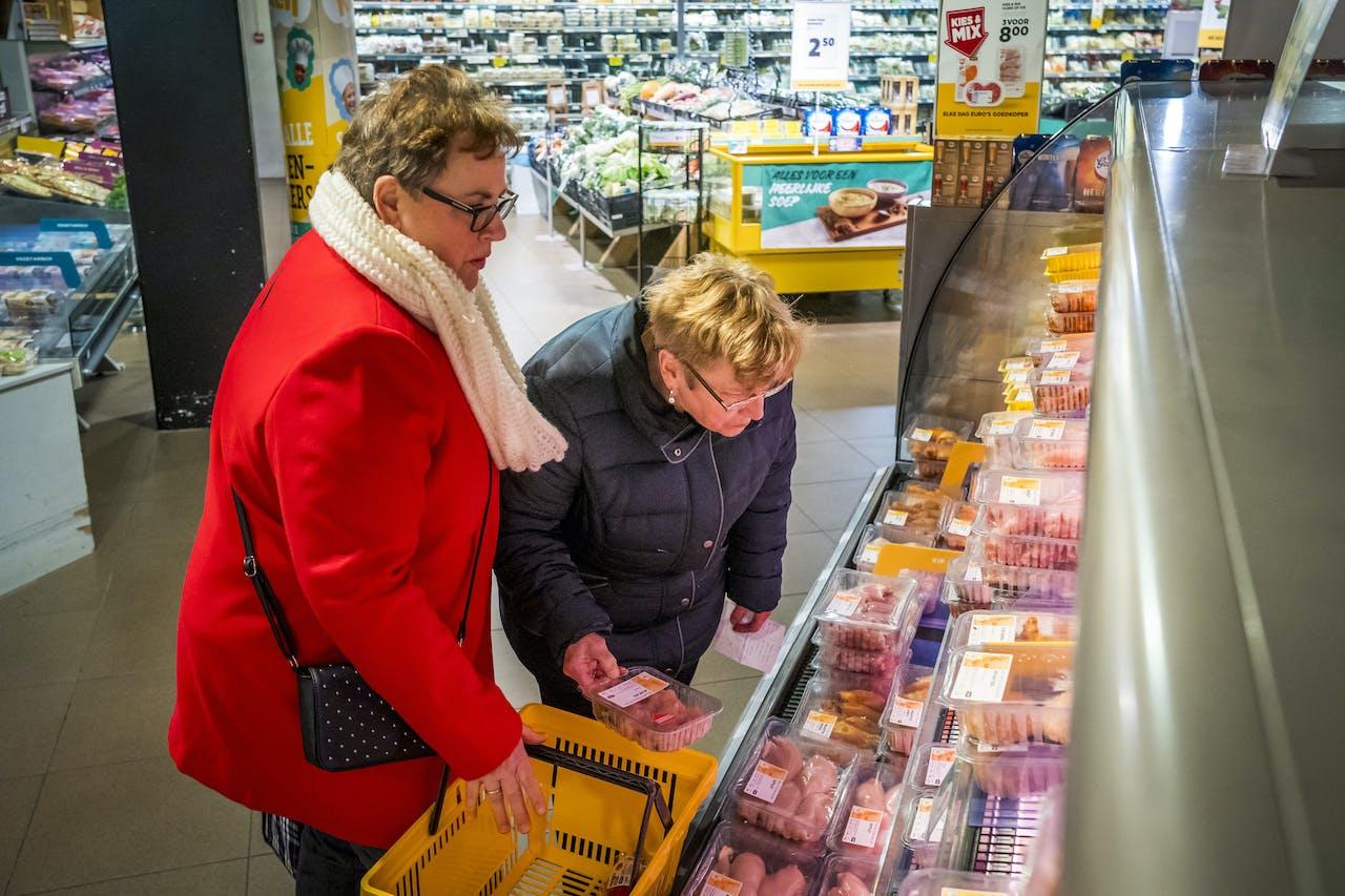 Twee vrouwen bij de vleesafdeling in de supermarkt.